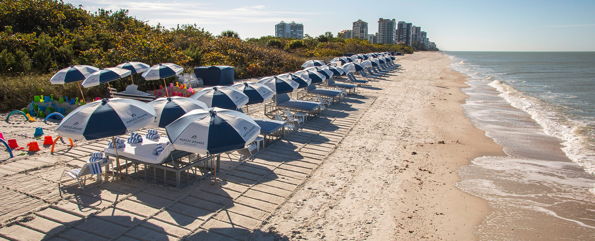 tables and beach chairs on naples grande beach