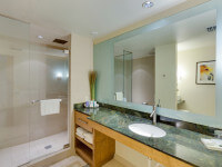 Spa-like bathroom with polished granite counters and natural stone