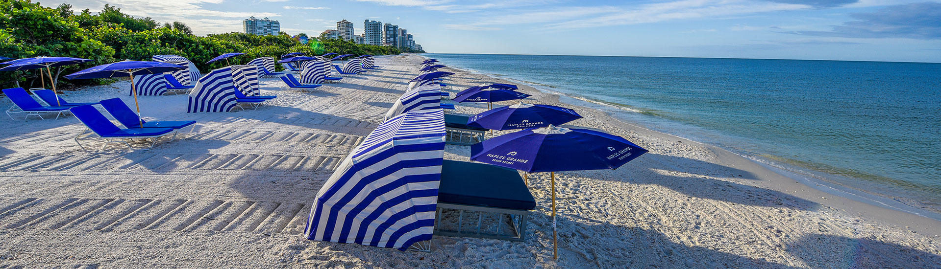 beach chairs and tables on naples grande beach